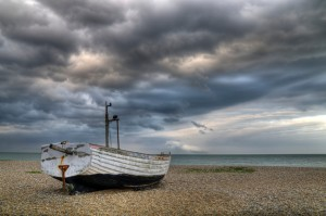 Single boat on a shingle beach with a stormy sky approaching.