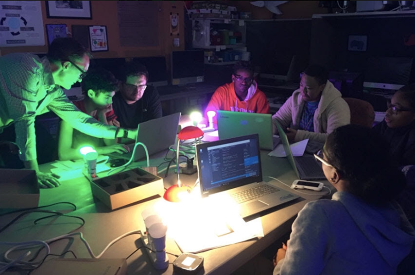 A building automation training instructor works with students on laptops programming wireless LED bulbs.